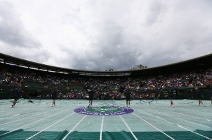 LONDON, ENGLAND - JUNE 28:  Groundstaff pull the rain covers on the courts as rain delays play on day six of the Wimbledon Lawn Tennis Championships at the All England Lawn Tennis and Croquet Club at Wimbledon on June 28, 2014 in London, England.  (Photo by Steve Bardens/Getty Images)