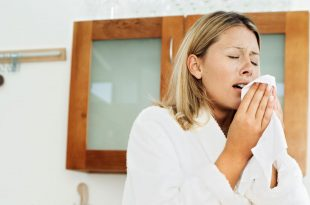 young woman in a bathrobe sneezing into a tissue