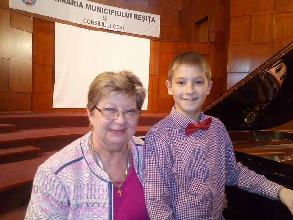 Elevul Costa Iosia, unul dintre cei patru elevi care au obținut premiul I și calificarea la faza națională a olimpiadei de interpretare instrumentală, alături de profesoara Doina Ona